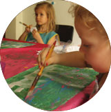 Two children painting at Ocarina School during an art discovery class.