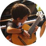 Child playing the guitar at Ocarina school during the guitar classes.